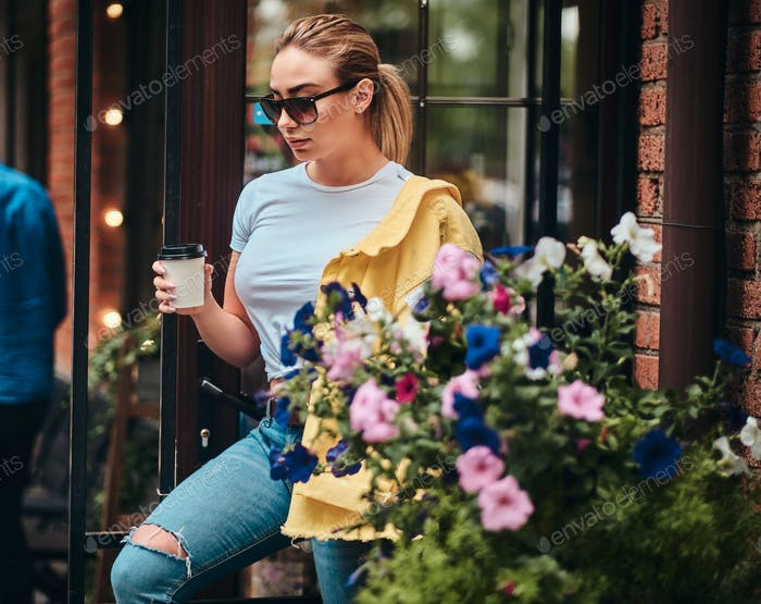 Junge Frau mit einer Tasse Kaffee zum Mitnehmen genießt den Sommer draußen.