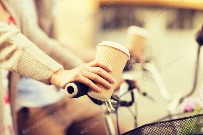 woman hand holding coffee and riding bicycle
