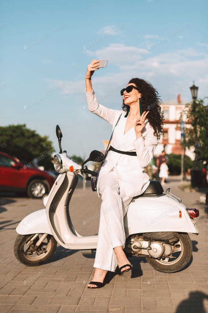 Pretty woman in white costume and sunglasses sitting on moped happily taking selfie in city center