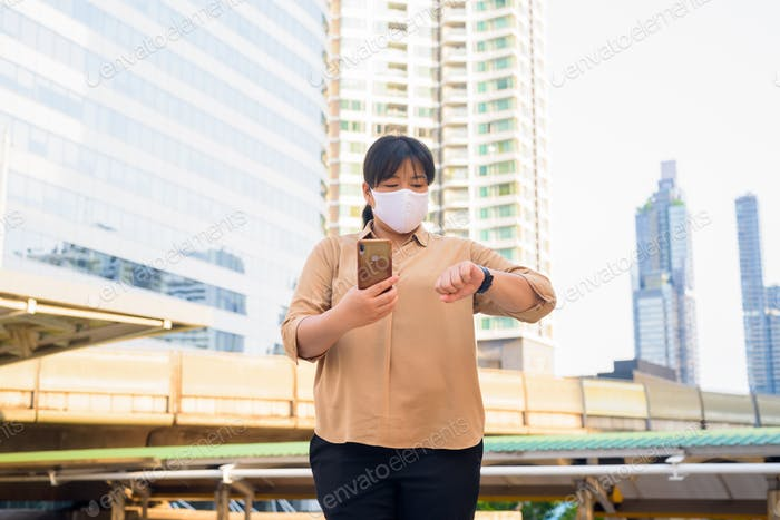 Overweight Asian woman with mask using phone and checking the time at skywalk bridge