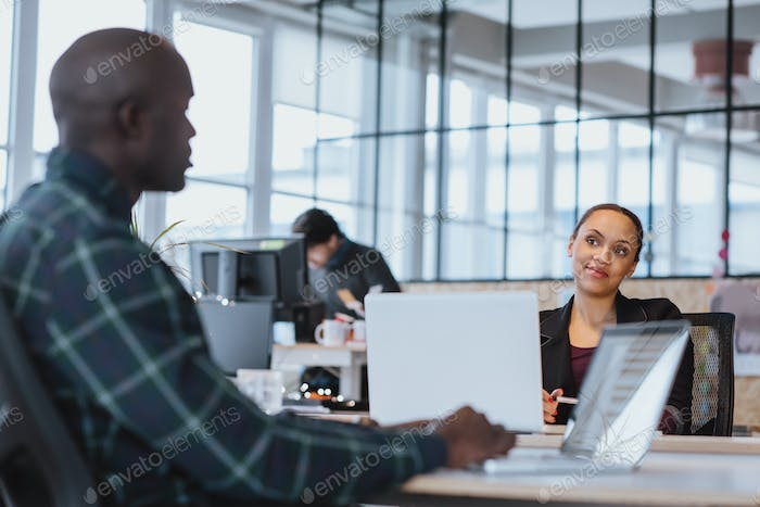 Executive discussing work with coworker in office