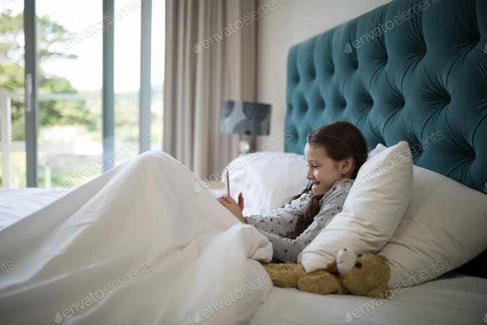 Girl using mobile phone on bed in bedroom