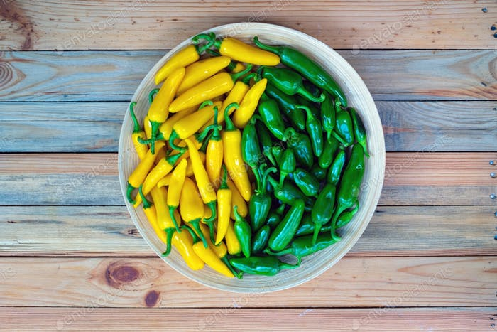 Yellow hot peppers on wooden plate
