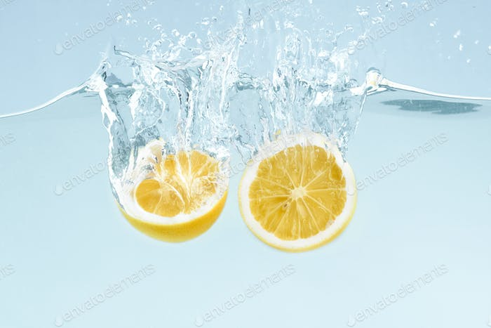 Citrus splash. Lemon halves splattering into clear water on blue background