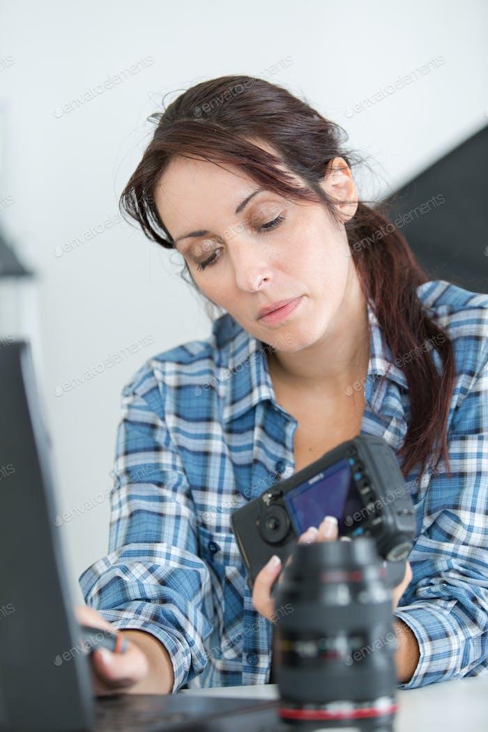 pretty technician examining dslr camera