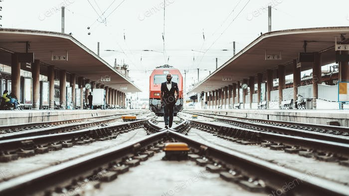 An African guy on the railway tracks