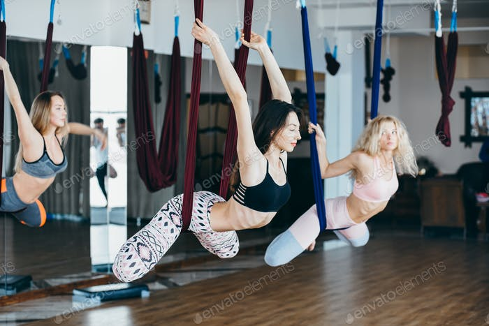Young girls do aerial yoga in the gym