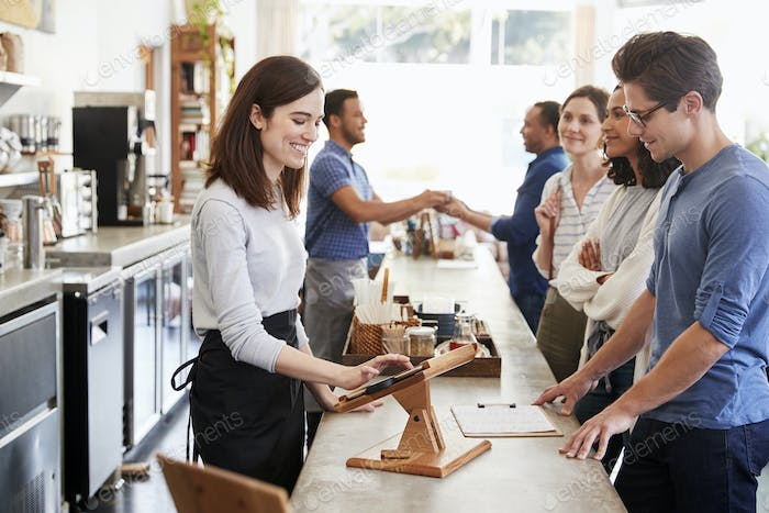 Customers queuing to order and pay at a coffee shop counter
