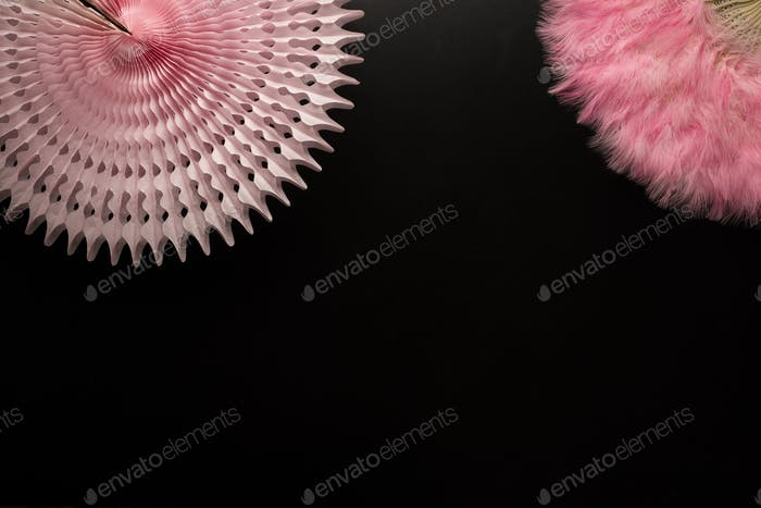 Carnival objects on a black background. Pink Chinese fan and paper star shape object