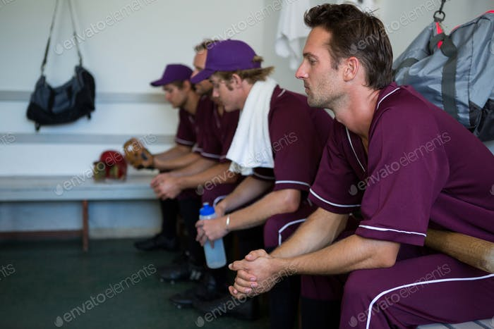 Side view of tired basball players sitting on bench