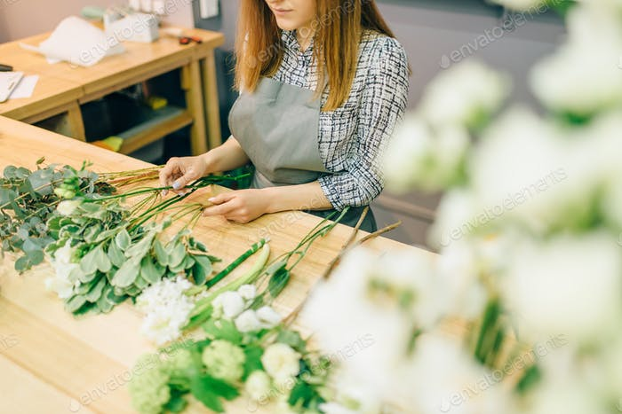 Female florist with plant bunches in hands