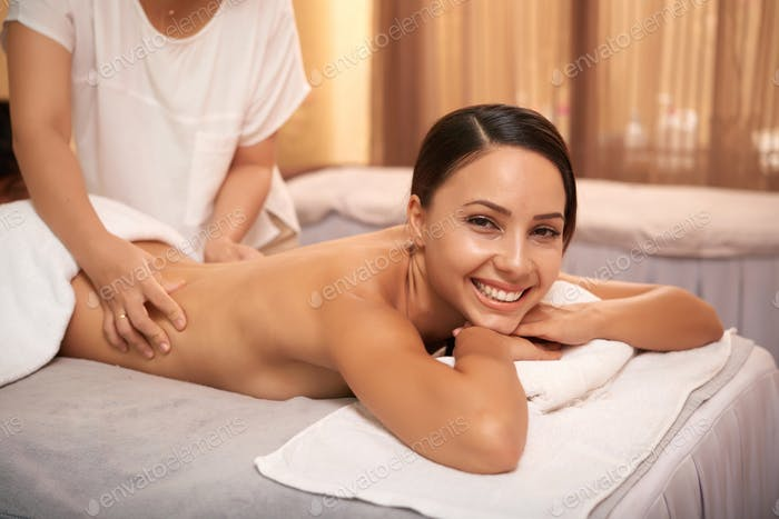 Woman getting massage for her back photo by DragonImages on Envato Elements