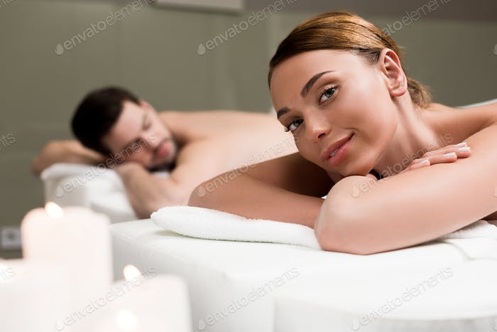 young woman smiling at camera while having massage in spa salon