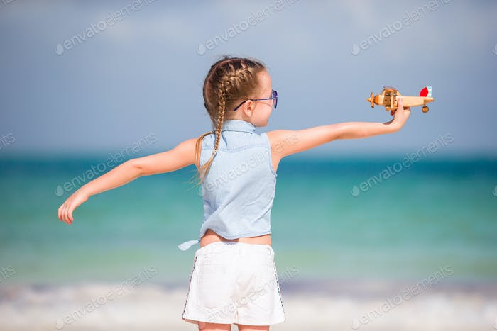 Happy little kid with toy airplane in hands on white sandy beach