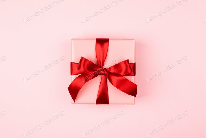 Pink Gift Box with Red Bow on Pink Background.