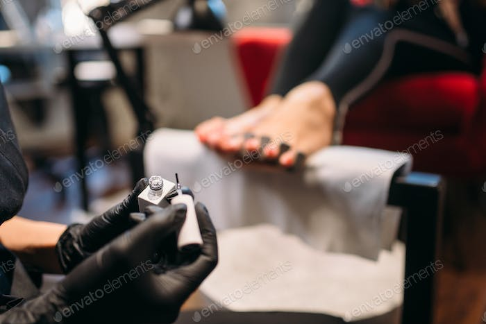 Pedicure master paints with varnish foot nails