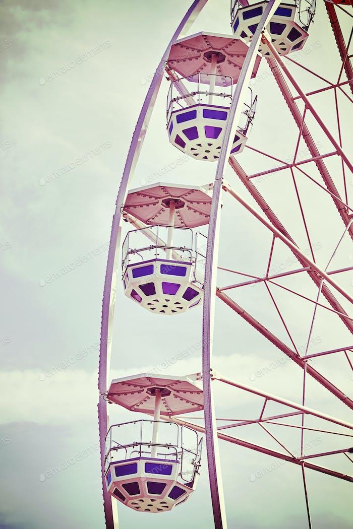 Retro toned picture of Ferris wheel cars