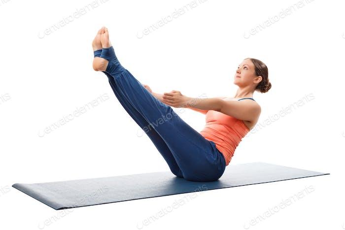 Woman practices yoga asana Paripurna navasana