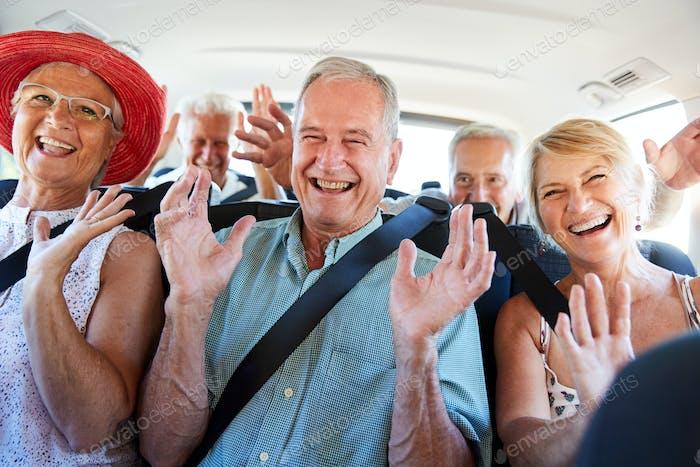 Vertical de mayores Amigos sentado en la parte de atrás de van siendo conducido a vacaciones