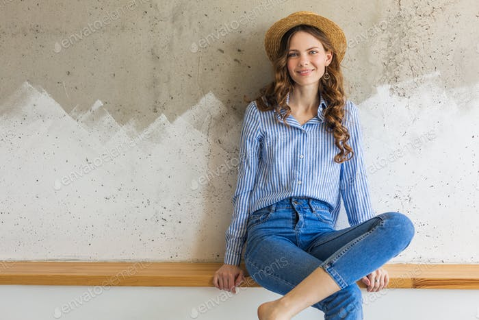 portrait of young pretty woman with straw hat jeans blue cotton shirt