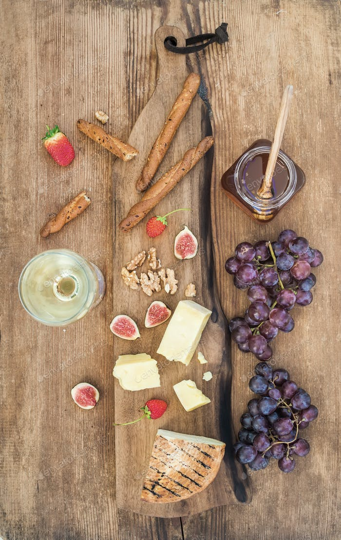 Glass of white wine, cheese board, grapes, figs, strawberries, honey and bread sticks