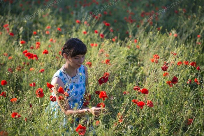 Beautiful woman on the poppy field.