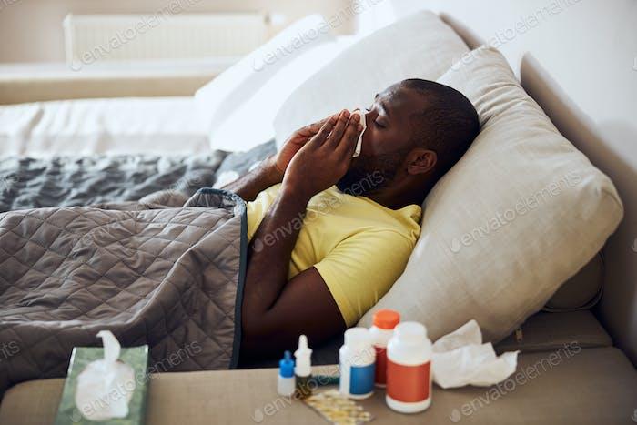 Kranke Person putzt sich die Nase liegend im Bett