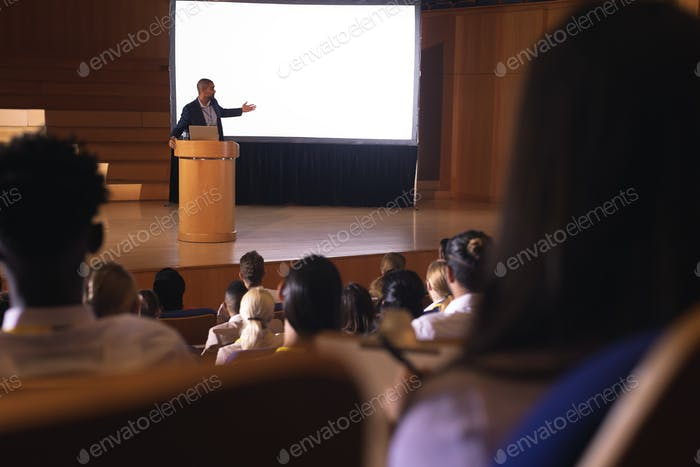 Audience sitting and listening while businessman standing near podium and giving presentation