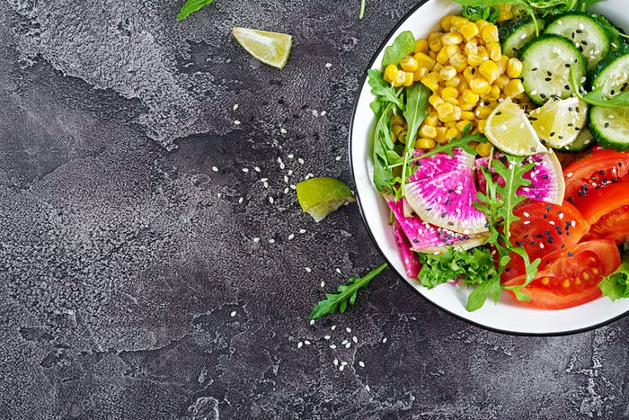 Schüssel mit frischem rohem Gemüse - Gurke, Tomaten, Wassermelone Rettich, Salat, Rucola und Mais.