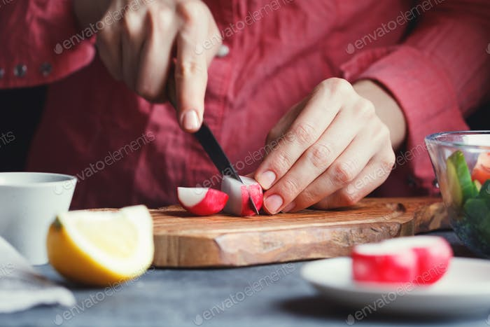 Girl in a pink shirt slices a fresh radish