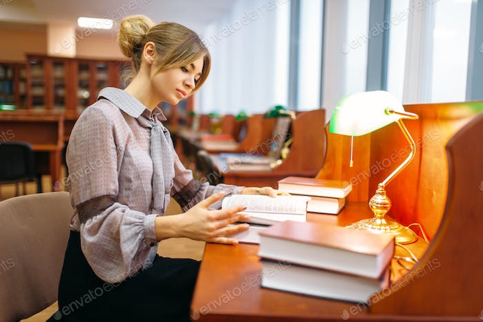 Woman reading book at the table in library