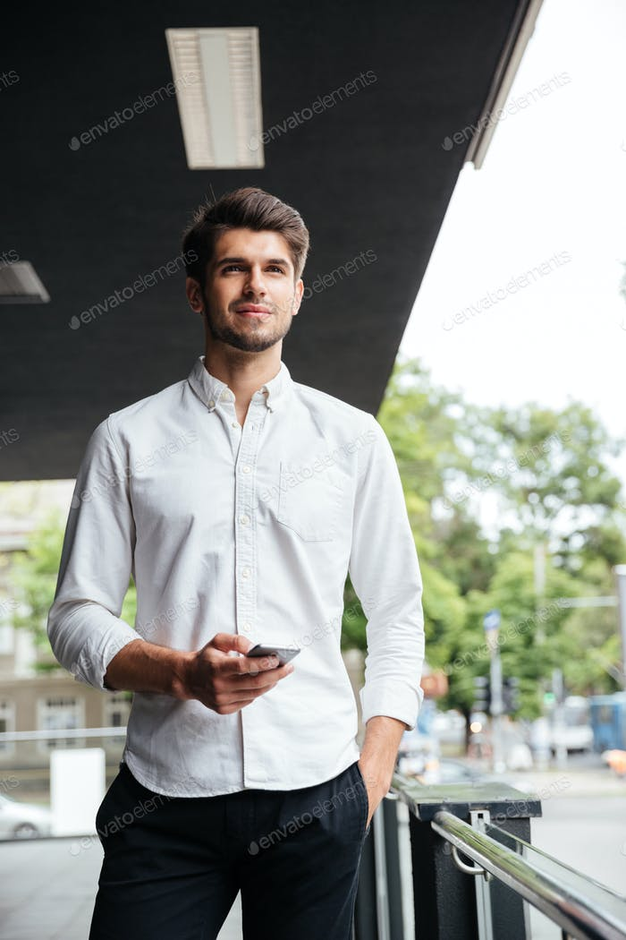 Businessman standing and using mobile phone near business center