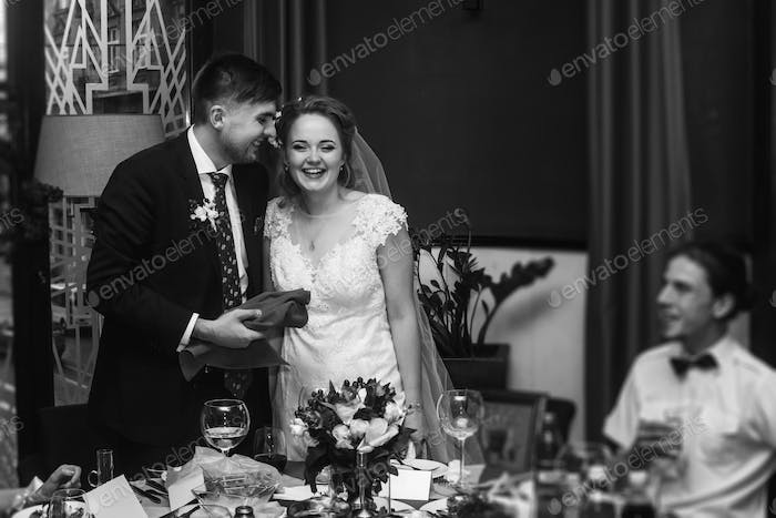 Newlywed couple laughing at wedding reception in restaurant