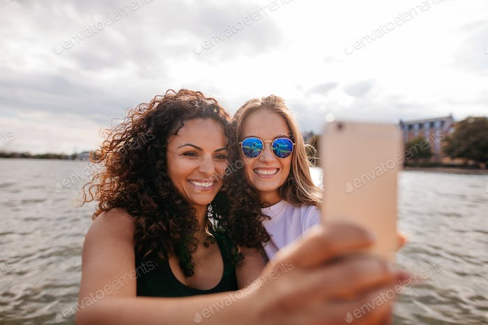 Attractive young women smiling and taking selfie