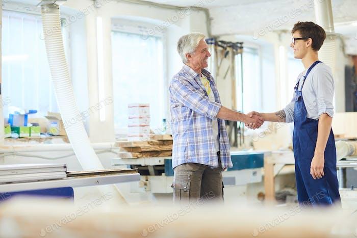 Cheerful mature carpenter making handshake with young employee