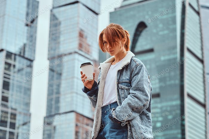 Stylish redhead hipster girl holding takeaway coffee in front of skyscrapers in Moscow city.