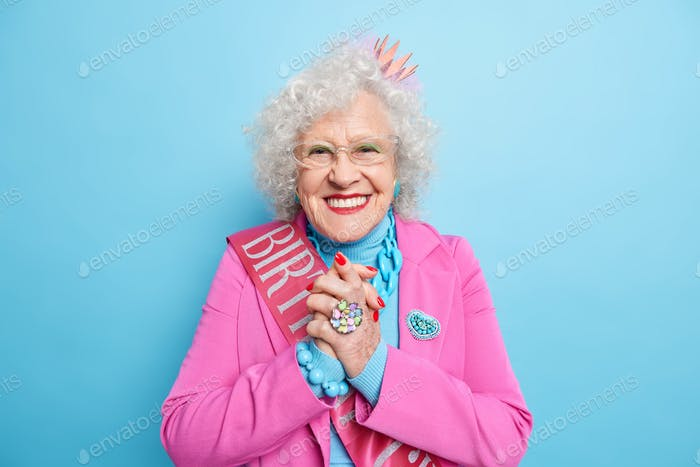 Optimistic smiling senior grandmother clasps hands and looks happily at camera wears festive costume