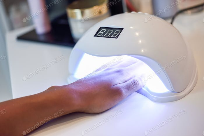 Manicured nails in UV lamp in beauty salon.