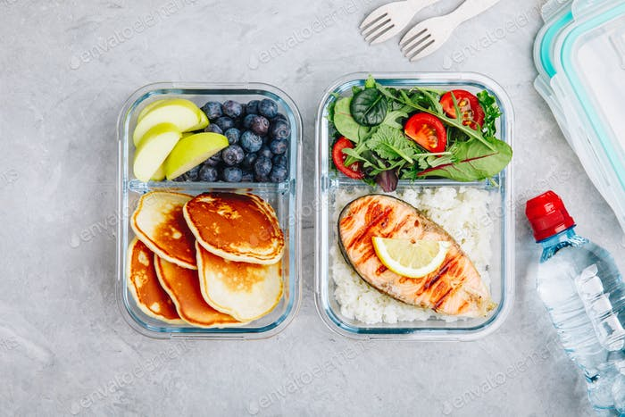 Meal prep containers with salmon, rice, green salad and pancakes, apple, blueberry.