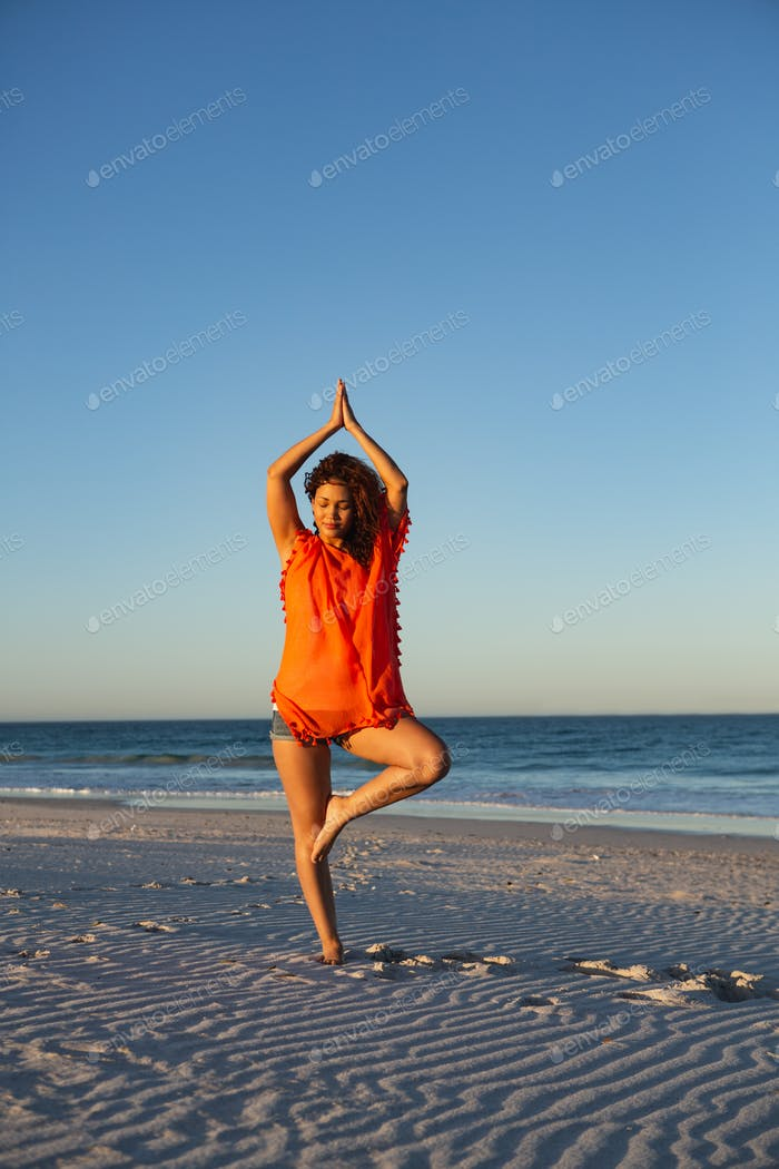 Front view of beautiful mixed race woman doing yoga on beach in the sunshine