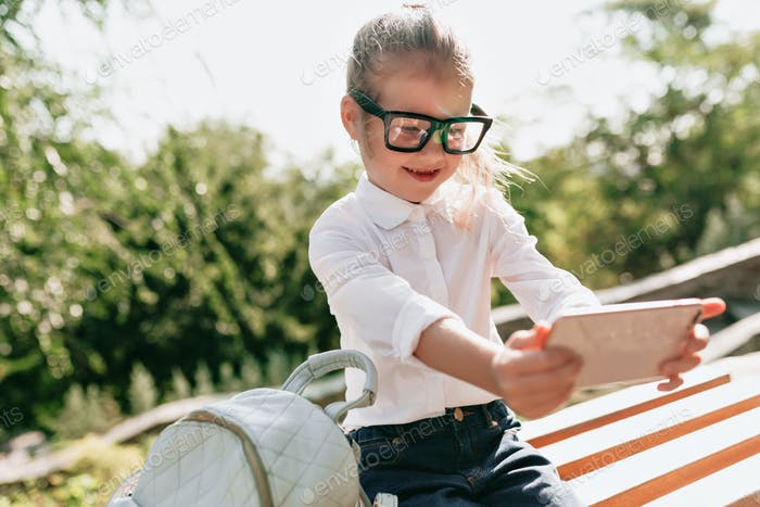 Incredible lovely smart girl in spectacles and white shirt preparing for study and school