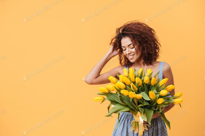 Attractive African woman  holding bouquet of flowers