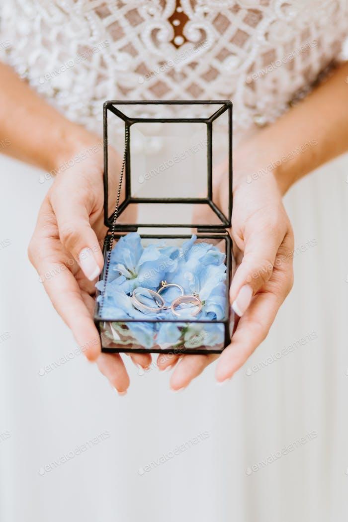 bride holding wedding ring box