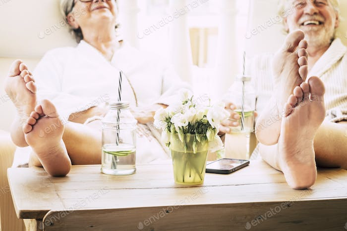 close up of feet of couple of seniors on the tale in a resort hotel or at home