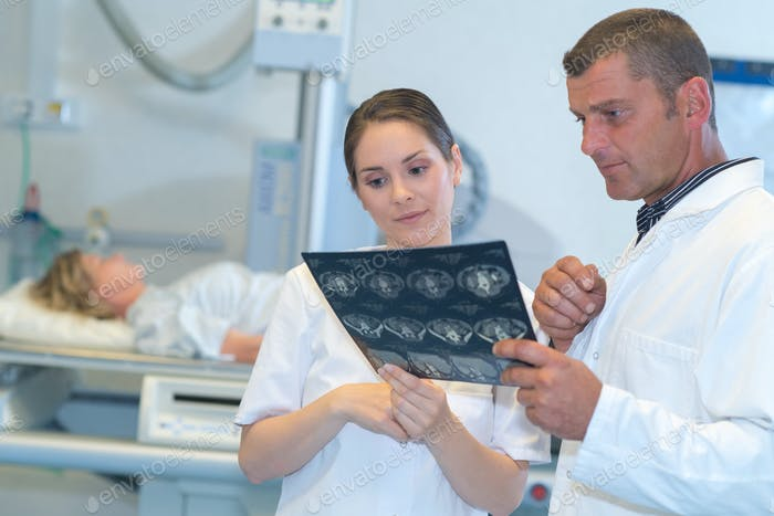 Arzt Analyse und Gespräch mit Assistenten über x-ray Ergebnisse