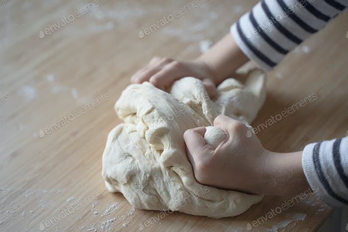 little Caucasian girl working the dough on a wood cutting board