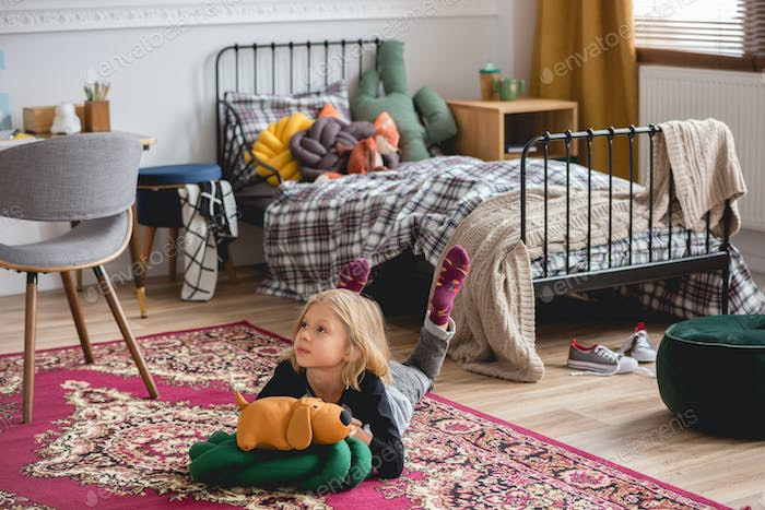 Cute blond girl on the floor of trendy child bedroom playing with her toys