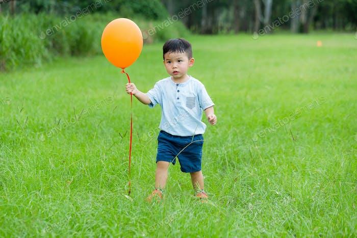 Little boy catching balloon