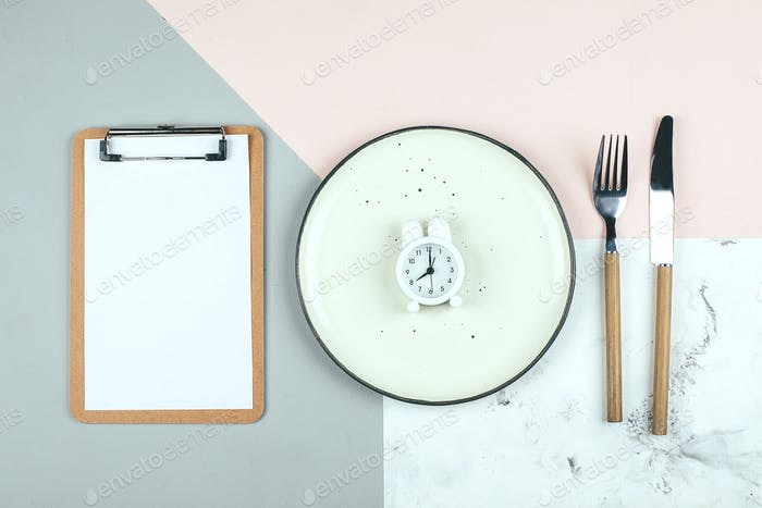 Intermittent fasting, ketogenic, diet concept. Plate with white alarm clock and white notepad