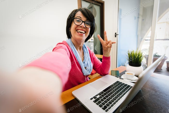 Mature older woman taking a selfie at home using computer technology.